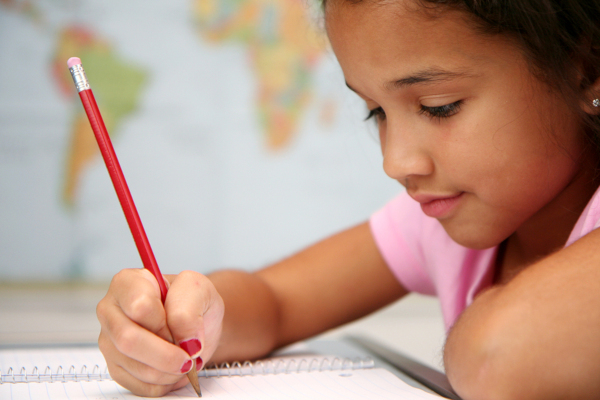 Young female child at school writing on paper