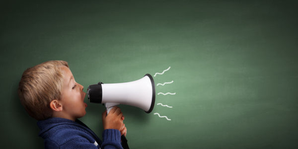 Child speaking through a megaphone against a blackboard