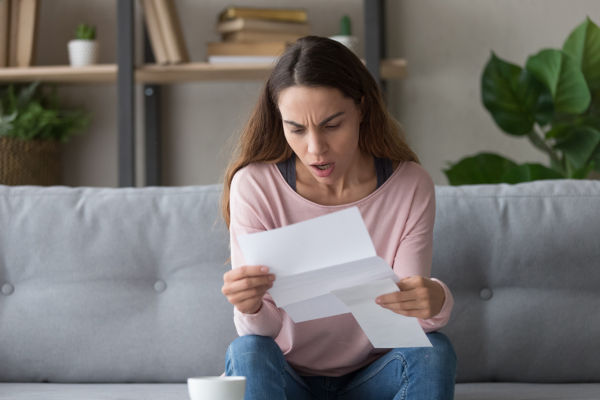 Shocked woman reading a letter