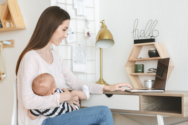 Woman holding sleeping baby whilst working on laptop