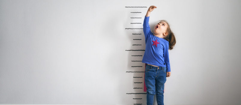 Child measuring how much they have grown