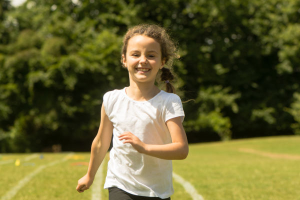 Young girl running at school