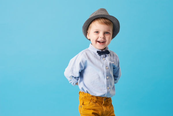 Happy little boy wearing a bowtie and hat