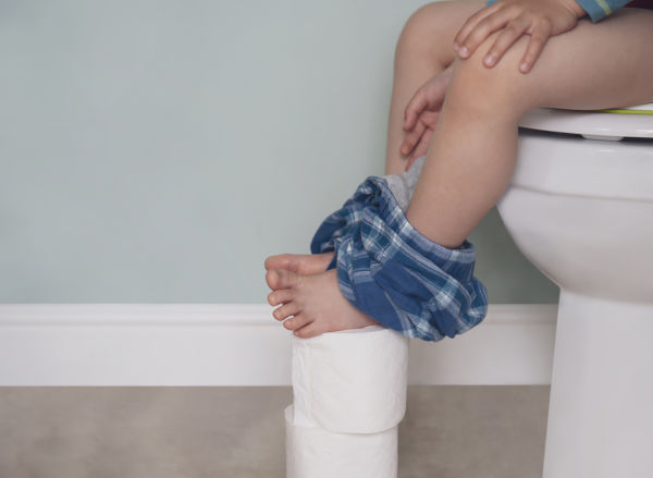 Child sat on toilet with bare feet
