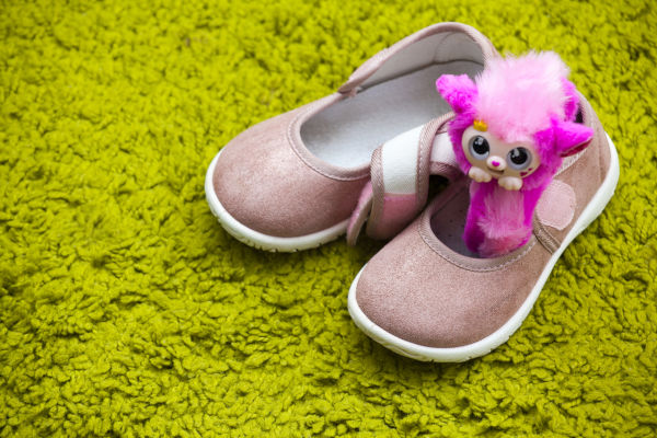Little girl's shoes with a pink toy inside