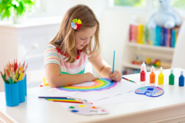 Girl painting a rainbow indoors