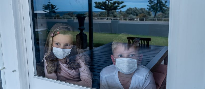 COVID-19 Lockdowns. Sad children with face mask looking through the window