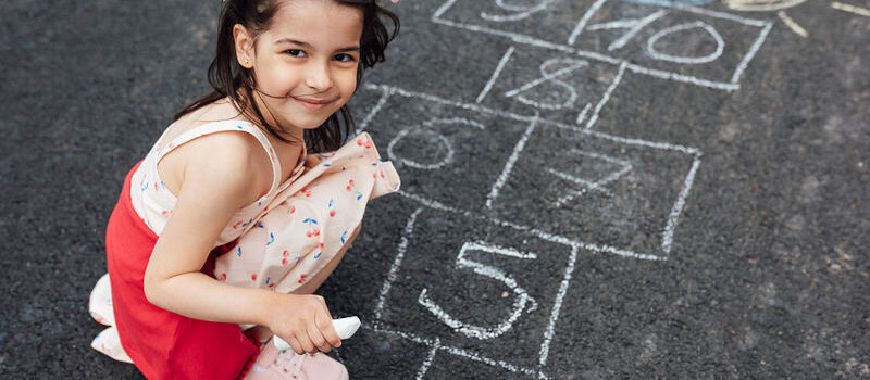 Smiling little girl drawing with chalk hopscotch on playground. Child playing the game outside. Kid wearing dress during playing hopscotch drawn on pavement. Activities for children.