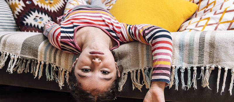 Bored girl hanging upside down over her bed