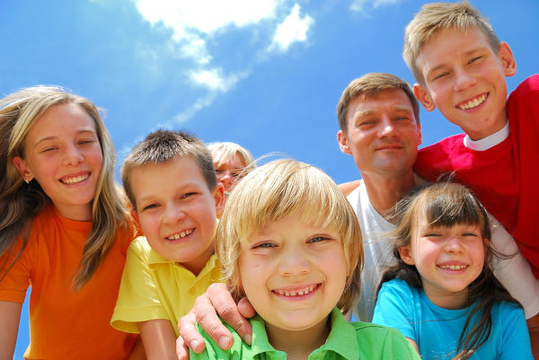 A family has fun outdoors crowding together and smiling into the camera.