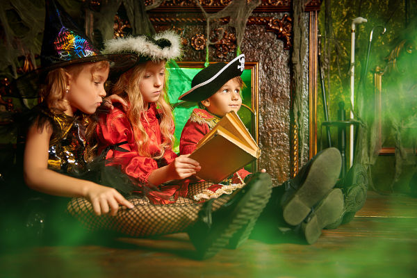 Children in carnival costumes sit together by the fireplace in an old house and read Halloween tales.