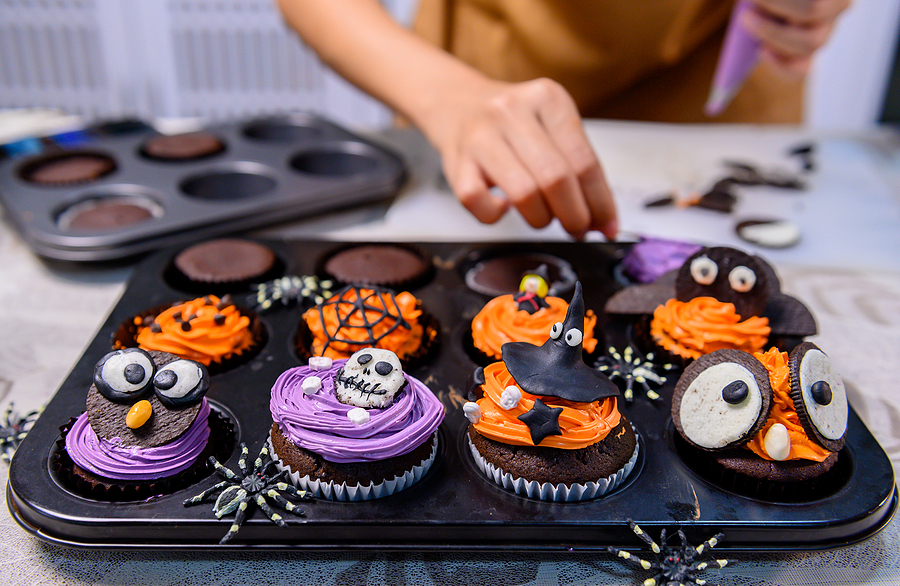 Cooking delicious homemade cake and decorate cupcake for Halloween festive. Preparing and mixing ingredients for sweet food dessert in kitchen at home.