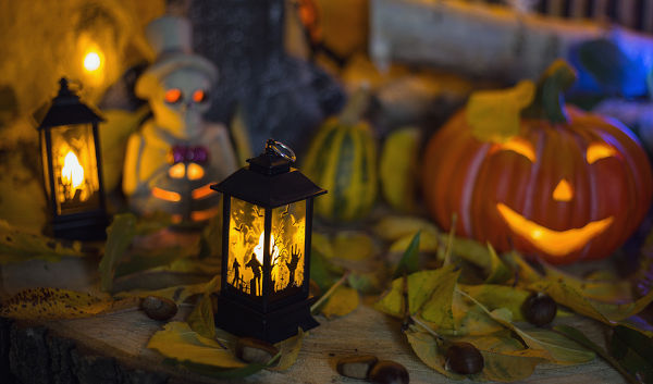 Halloween decorations concept at night. Close up of jack o'lantern, vintage lanterns, pumpkins, skull, autumn leaves. Colorful halloween lights on evening. Happy Halloween scene on wooden background