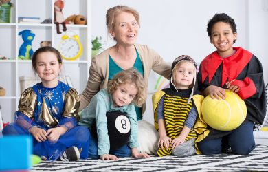 Dressed up children in colorful costumes and happy kindergarten teacher