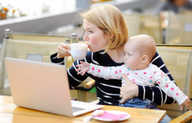 Tired young mother working oh her laptop holding daughter and drinking coffee