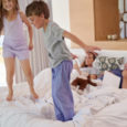 Happy children boy and girl siblings jumping on parents bed