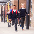 Children in school uniform running, leaving school