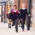 Children in school uniform running, leaving school