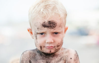 Little boy covered in sand at the beach