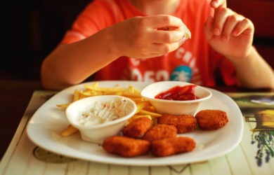 Boy eating chicken nuggets and chips