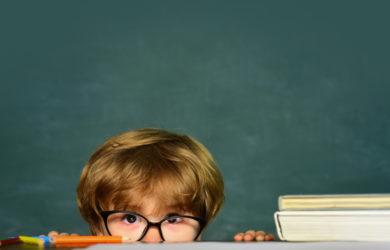 Boy peeking over the teacher's desk