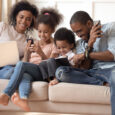 Happy family playing on different devices